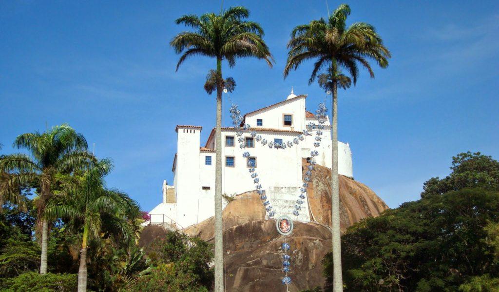 Fachada do Convento da Penha fica cravada em uma rocha e é branco. Dois coqueiros são vistos da frente e, entre eles, existe um terço enorme