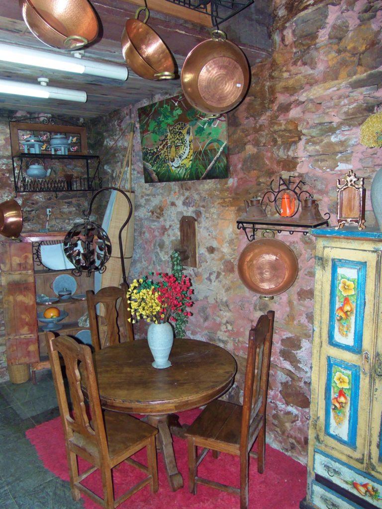 Panelas de cobre, conjunto de mesa e cadeiras de madeiras estão dentro da casa de Aleijadinho