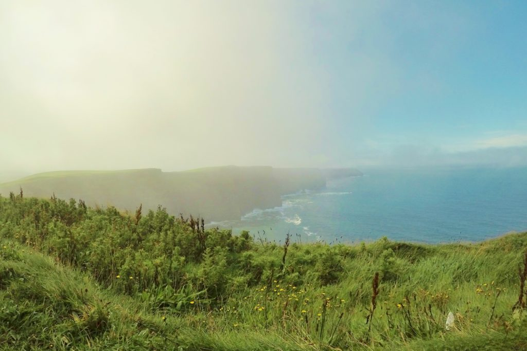 Do precipício gramado é possível ver rochas, uma atrás da outra, formando Cliffs of Moher